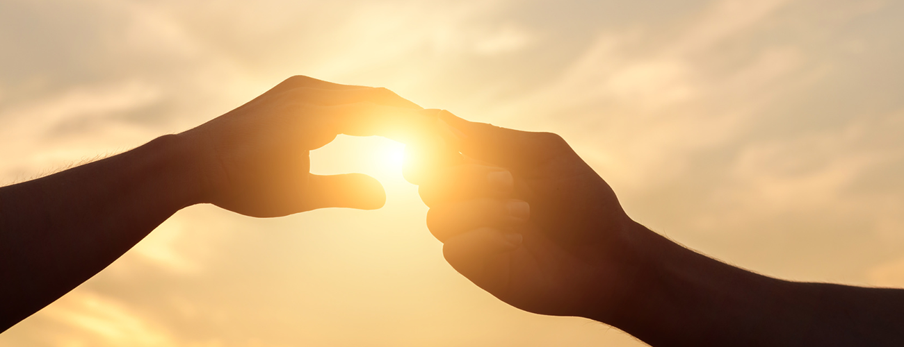 hands holding with sun in background