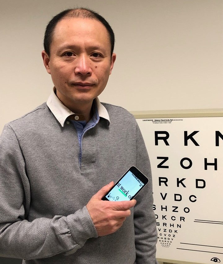 Dr. Gang Luo in front of eye poster holding smart phone with vision app