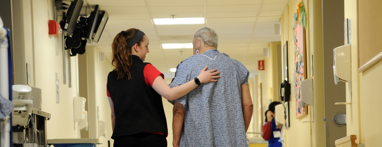nurse walking down hallway with adult patient